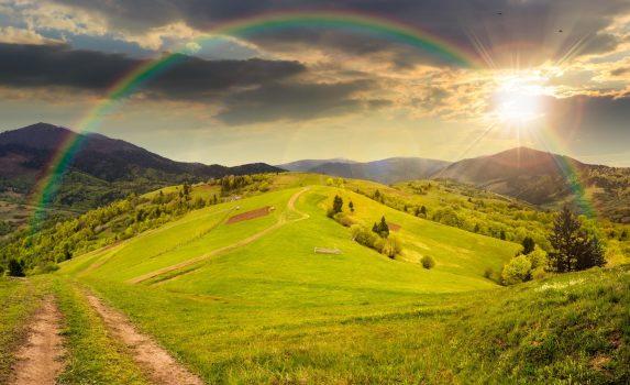 丘の上の牧草地と虹のかかる夕焼けの山々