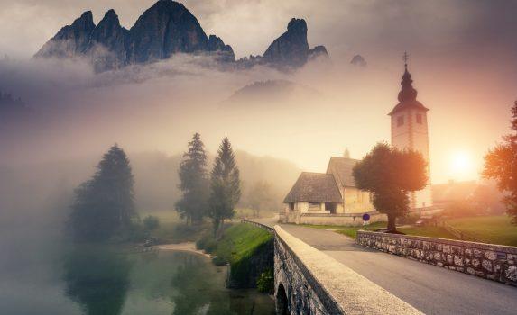 霧の朝のトリグラウ国立公園 ジュリア・アルプス山脈と教会の風景 スロベニアの風景