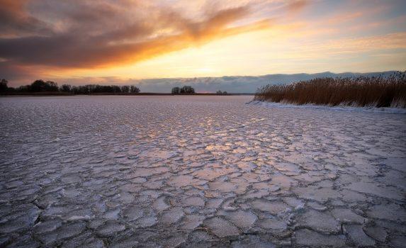 凍りついた湖と夕焼け空 冬の風景